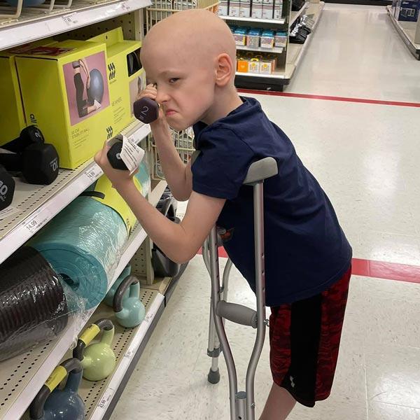 Pediatric cancer survivor Aiden on crutches