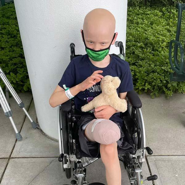 Pediatric cancer survivor Aiden in a wheelchair